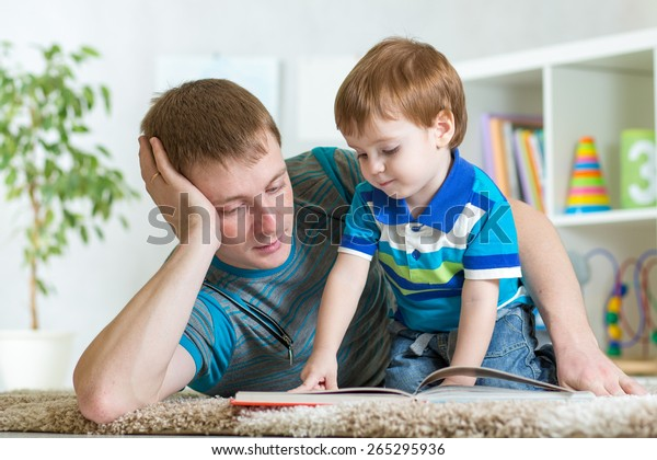 kid boy and his father read a book on floor indoors