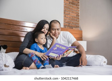 Kid boy and his father reading a book in bed accompanied by mom