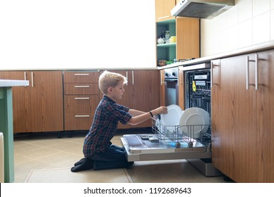 Kid boy in kitchen getting out clean crockery of dishwasher. Concept of kid cleaning dishes after eating