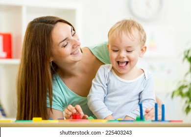kid boy and mother playing at table at home