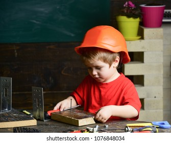 Kid boy in orange hard hat or helmet, study room background. Childhood concept. Boy play as builder or repairer, work with tools. Child dreaming about future career in architecture or building.