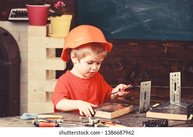 Kid boy in orange hard hat or helmet, study room background. Boy play as builder or repairer, work with tools. Child dreaming about future career in architecture or building. Childhood concept.