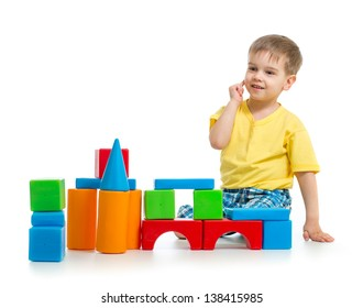 kid boy is playing with colorful building blocks isolated on white
