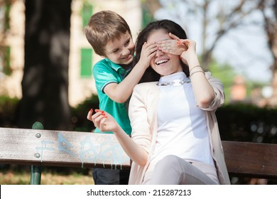 kid boy playing in the park guess who with his young mom or aunt