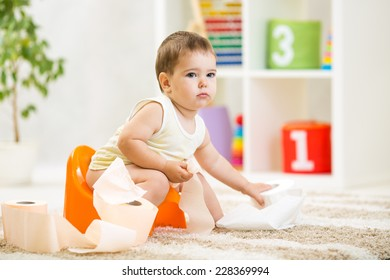 kid boy sitting on chamber pot with toilet paper roll