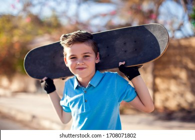 Kid boy with skateboard on the street. Childhood, leasure and lifestyle concept