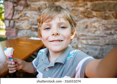 Kid boy taking selfie with mobile phone during eating ice cream on summer day. happy blond child having fun.