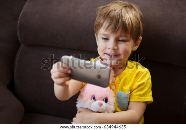 Kid boy taking selfie with mobile phone embracing a favourite toy. happy child having fun.