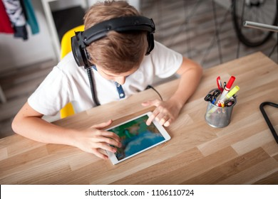 Kid boy using tablet with headphones sitting at desk in his room