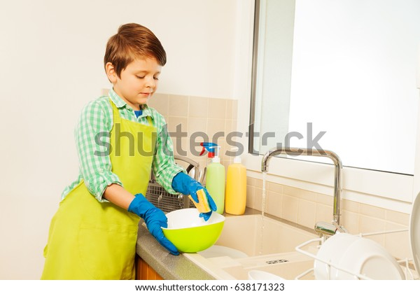 Kid boy washing dishes under running water
