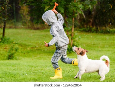 Kid boy wearing waterproof coat playing with dog under rain