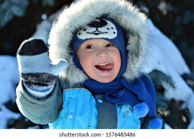 Kid boy in winter clothes playing with snow and catching snowflakes his tongue. Hallo winter concept.