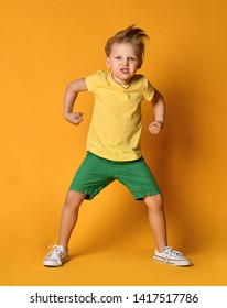 Kid boy in yellow t-shirt and green shorts poses with clenched fists is ready to fight demonstrates power and hisses with rage on yellow background