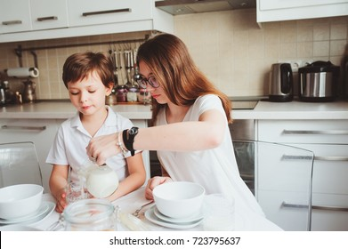 kid brother and teen sister having breakfast at home in modern white kitchen and eating snacks. Casual lifestyle in real life interior
