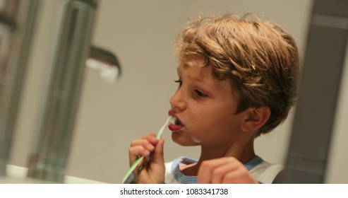 Kid brushing teeth in front of mirror