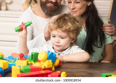 Kid with busy face plays with plastic bricks on light background. Family spend time together in playroom. Childhood concept. Parents watch their son hold constructions made out of colorful blocks.