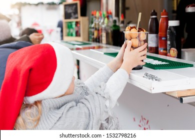 Kid is buying street food at Christmas market. Cute child with italian festive sweets, fritters, chocolate doughnuts outside in old town. Fair atmosphere in Dubrovnik, Croatia