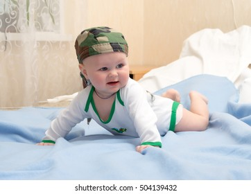 Kid in the camouflage bandanna plays lying on his stomach