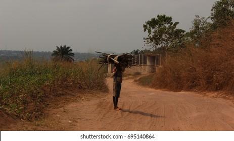 Kid carrying heavy wood near Kasangulu, outskirts of Kinshasa. Republic Democratic of Congo.