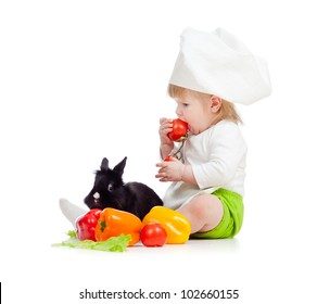 Kid in chef hat with healthy food and rabbit