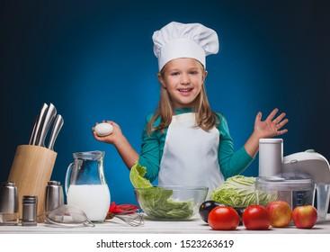 Kid Chef prepares a delicious dish on a blue background.studio portrait