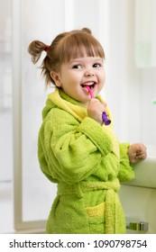 kid child girl brushing teeth in bathroom