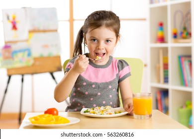 kid child girl eating healthy food at home