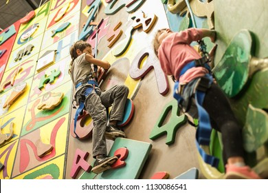 kid, child having fun on a climbing wall in an indoor climbing center, active healthy lifestyle, active children in sports