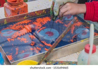"""Kid child learning the turkish water painting named """"Paper marbling"""" technique method of aqueous surface design, which can produce patterns similar to smooth marble. Paper water painting art course"""