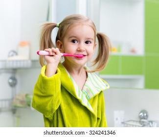 Kid child little girl brushing teeth in bathroom