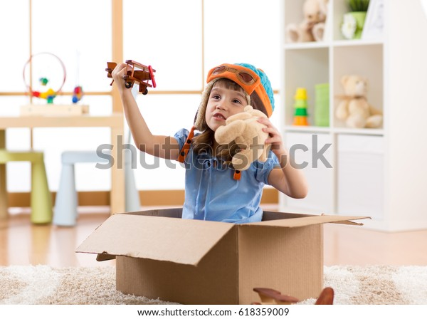 Kid child pilot flying a cardboard box in kid room