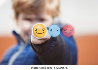 Kid choosing smiley face emoticon on virtual touch screen.