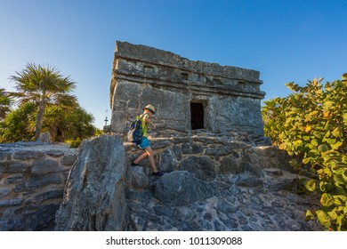 Kid climbing on the top of antique ruins