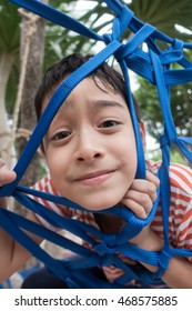 Kid climbing on the tree with rope net outdoor activity