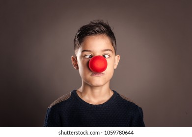 kid with a clown nose on a gray background