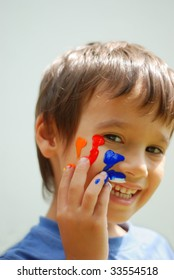 Kid with color on his fingers and face smiling