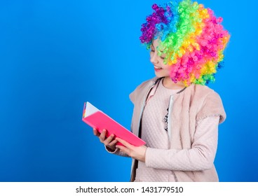 Kid colorful curly wig artificial hair clown style hold book. Reading jokes. Time to have fun. Circus school. Study hard. Ridiculous story. Reading funny book. Literature club. Jokes book concept.