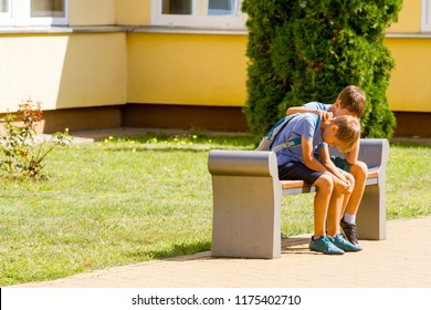 Kid comforting consoling upset sad boy in school yard