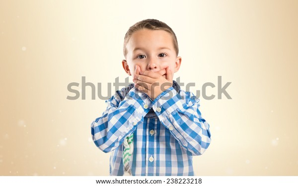 Kid covering his mouth over ocher background