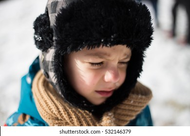 kid crying after being hit in the eyes with a snowball