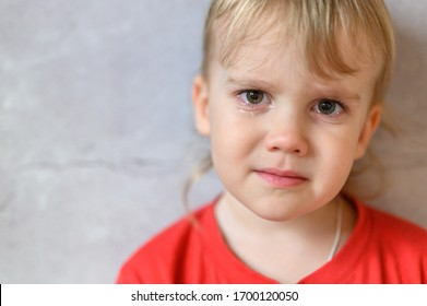 kid crying. the face of a cute little upset four year old baby boy in tears. children's grief. gray concrete wall background. space for text