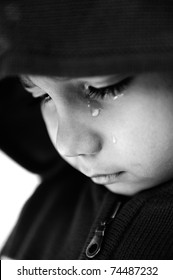 Kid crying, focus on his tear, added a bit of grain, black and white