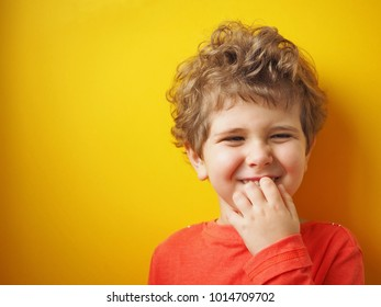 Kid with curly hair makes a fanny face. Yellow background.