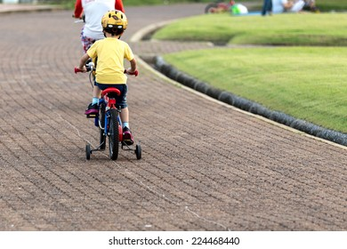 Kid is cycling in the park