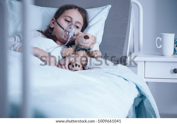 Kind mit Mukoviszidose, das in einem Krankenhausbett mit Sauerstoffmaske und Spielzeug liegt