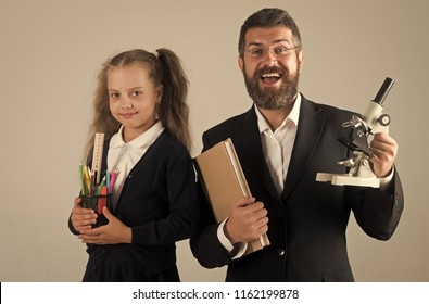 Kid and dad hold book, pencils and microscope. Home schooling and back to school concept. Father and schoolgirl with happy and cunning faces on grey background. Girl and man in suit and school uniform