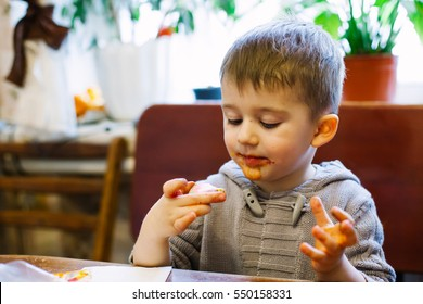 Kid decorating gingerbread shapes with a food coloring