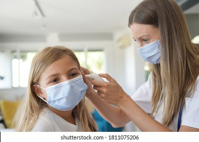 Kid at doctor's office with protection face mask having temperature checked - Shutterstock ID 1811075206