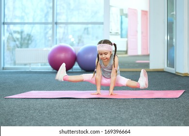 Kid doing fitness exercises on the mat