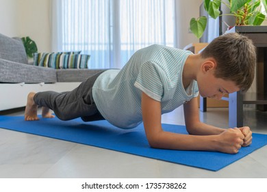 Kid doing sport exercises on mat at home. Sport, healhty lifestyle, active leisure at home